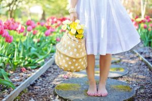 Lady in a white dress walking barefoot on a stone footpath with blooming flowers on the side.